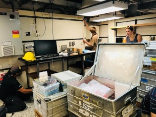 "Shreyas, Shane, and Sara unloading gear in the ""Hydrolab,"" one of the many lab spaces on the R/V Thompson"