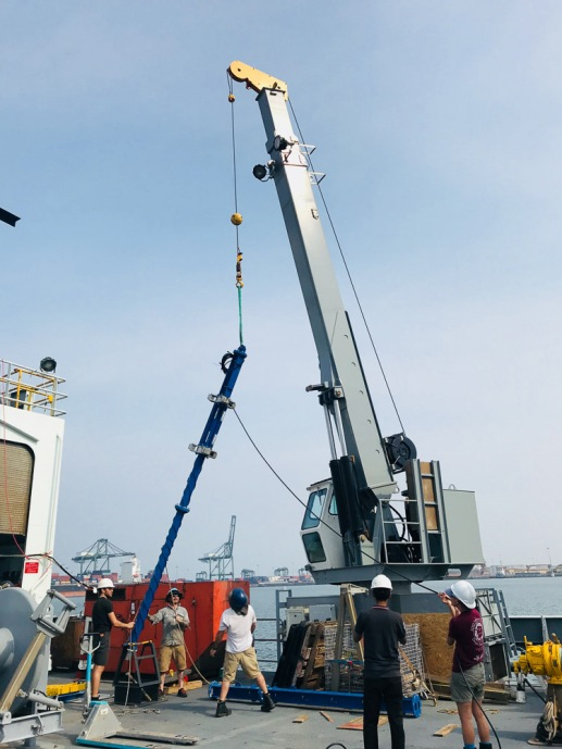 Yes, there is a crane on this ship! Here, the giant blue pole is being lowered into the ocean below the ship. At the end of the pole, we will attach an instrument that counts fish of different sizes.